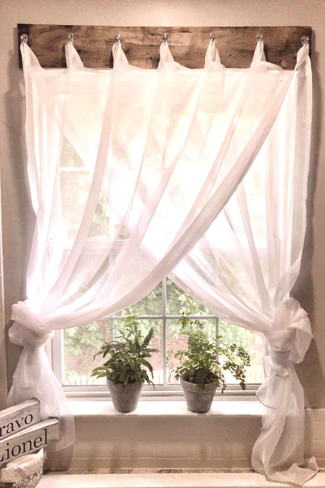 beautiful farmhouse window treatment using reclaimed wood and sheer curtains